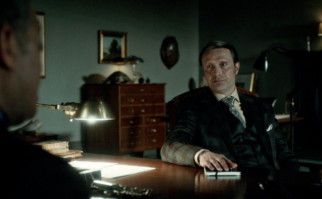 Suit xanh rêu đi với sơ mi màu kem và cà vạt paisley, một trong những bộ đẹp nhất của Hannibal.