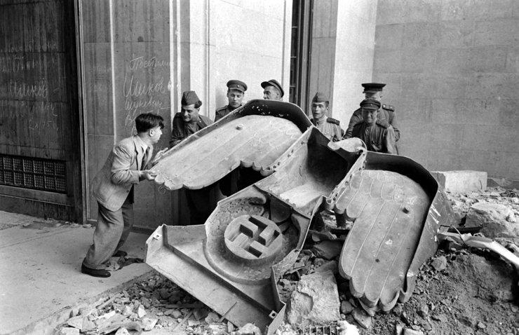 Lính Nga và thường dân Đức di chuyển biệu tưởng đại bàng của đảng quốc xã ra khỏi phủ thủ tướng ở Berlin, 1945.
