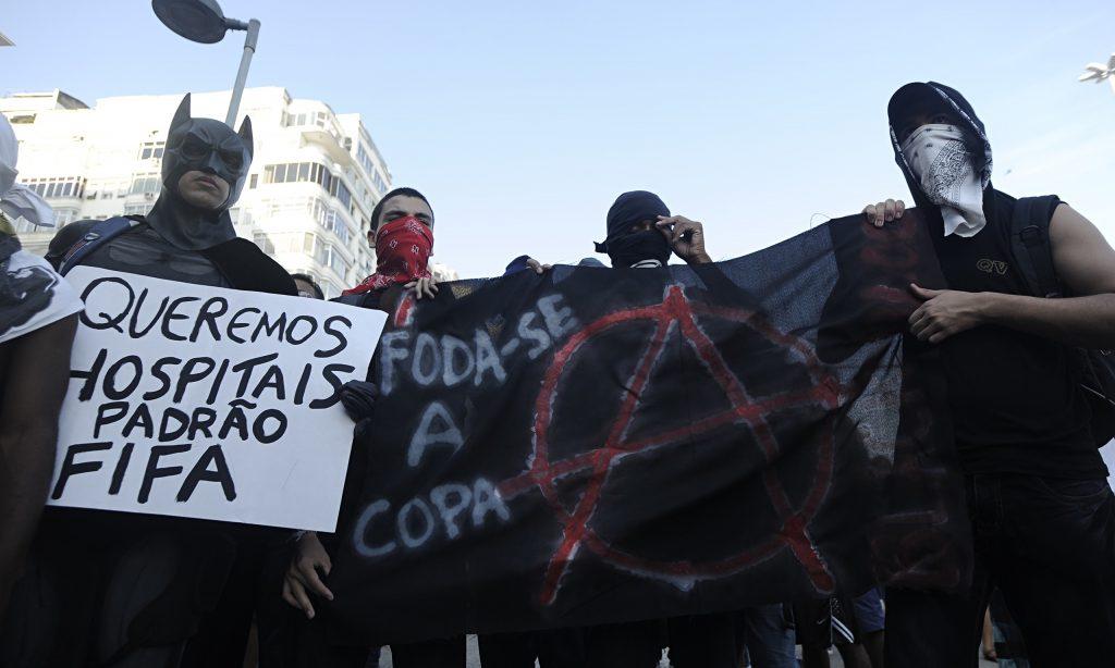 """""""Batman"""" Melo tham gia biểu tình Black Bloc cùng người dân. Black Bloc là một hình thức biểu tình mà những người tham gia đều mặc quần áo đen, đeo khăn che mặt hoặc kính râm, mũ bảo hiểm và các thiết bị phòng hộ khác để che giấu danh tính và bảo vệ mình khỏi hơi cay và bom khói của cảnh sát."""