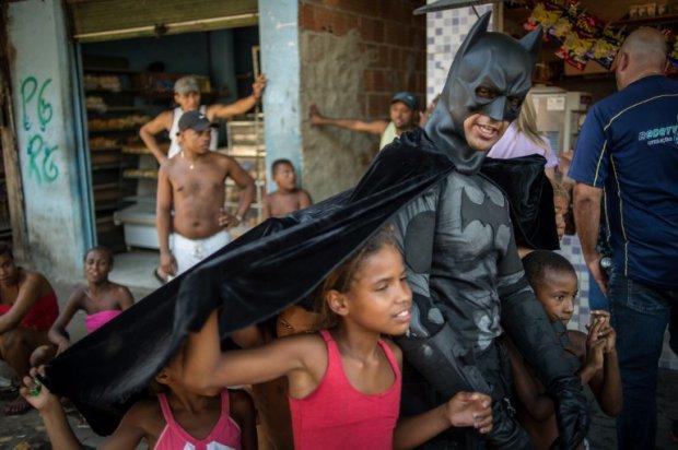 Batman của Rio de Janeiro chơi đùa cùng trẻ em ở khu ổ chuột Favela gần sân vận động Maracana.