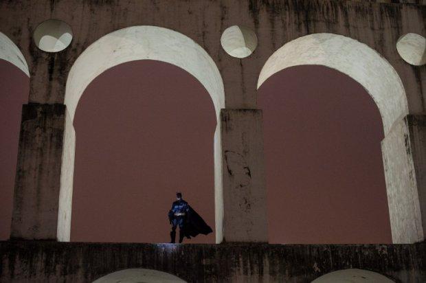 """""""Batman"""" Melo đứng trên cầu dẫn nước ở Lapa, Rio de Janeiro trong một phút yên lặng giữa cuộc biểu tình dữ dội về đêm."""