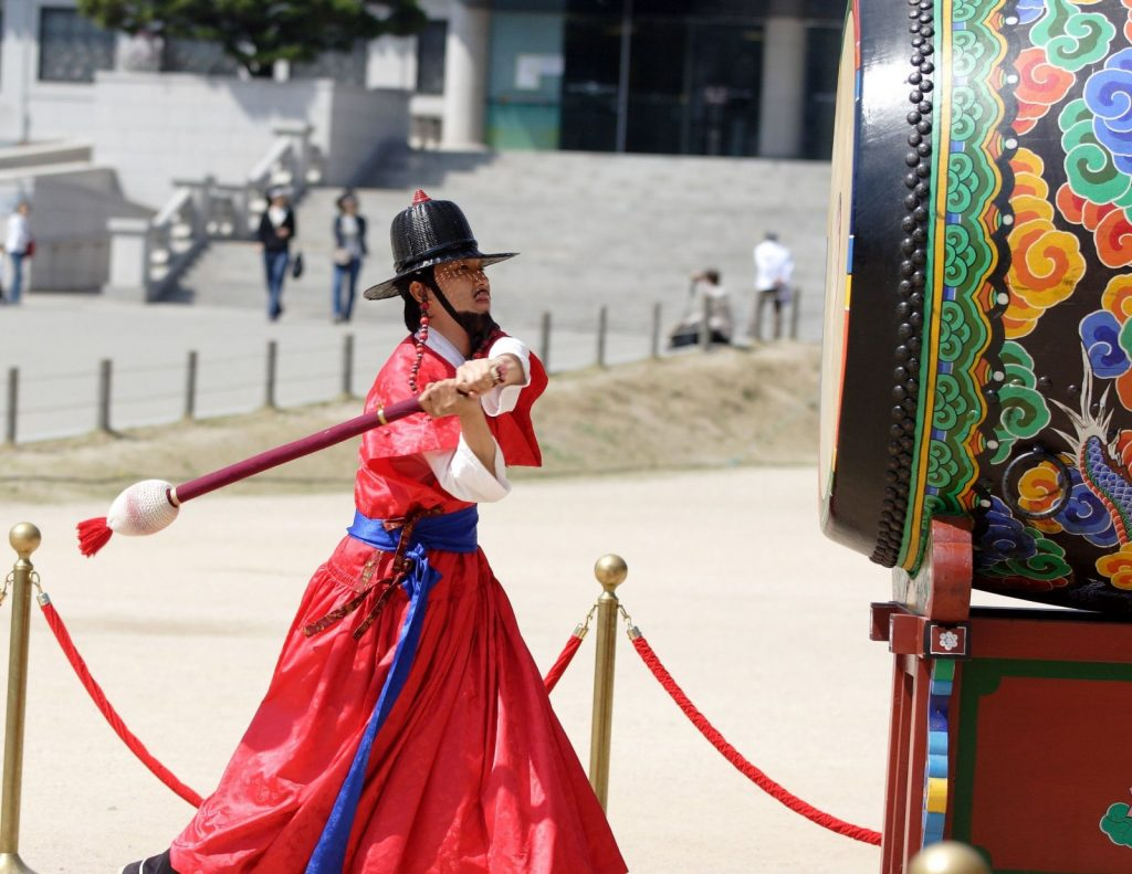 korean-man-in-traditional-costume-beats-the-drum-to-signal-the-changing-of-the-guard-at-kyoungbok-palace-in-Seoul-Korea-1600x1236