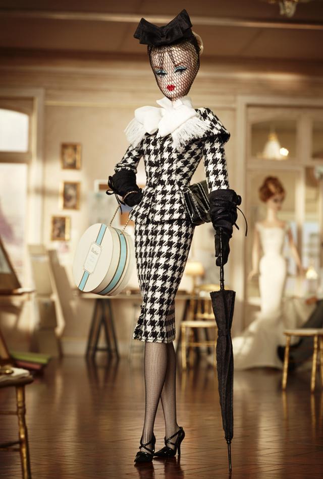 Barbie lững thững bước đi trong bộ suit mang họa tiết houndstooth, chấm phá với vòng nơ trắng bản to. Phụ kiện hợp lý, chiếc ô, mũ đen che mạng... càng tôn vẻ quyết đoán và quý phái.