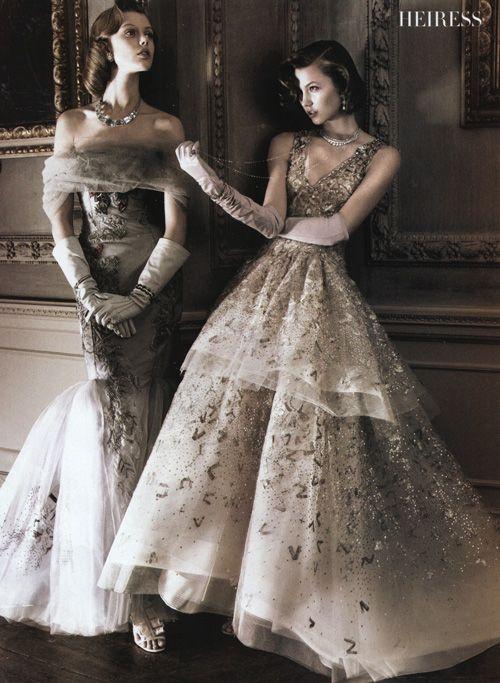"""David Sim với bộ Editorial """"The American Experience"""" cho Vogue US tháng Năm, 2010 đưa chúng ta đến với hành trình xuyên suốt qua các số báo Vogue US, từ thuở sơ khai cho đến giai đoạn hiện đại bằng những thiết kế mới lạ dựa trên những góc nhìn cổ điển. Trong ảnh: bên trái là Frida Gustavsson với váy Tulle thêu của Caroline Herrera. Bên phải là Karlie Kloss mặc váy Oscar de la Renta. Trang sức: Sandra Cronan."""