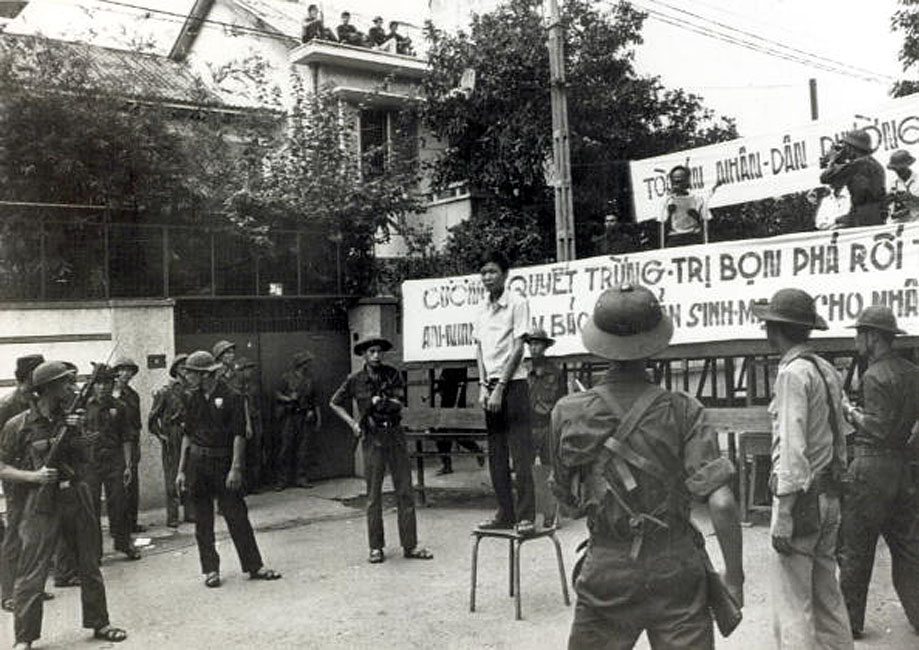 June 1975, Nguyen Tu Sang, Saigon, Vietnam, A man stands on a chair, convicted of armed robbery as an official reads his sentence from a platform, as communist forces prepare to act as a firing squad and carry out the sentence of death (Photo by Rolls Press/Popperfoto/Getty Images) SAIGON (AP) - Họ đã đến xem một