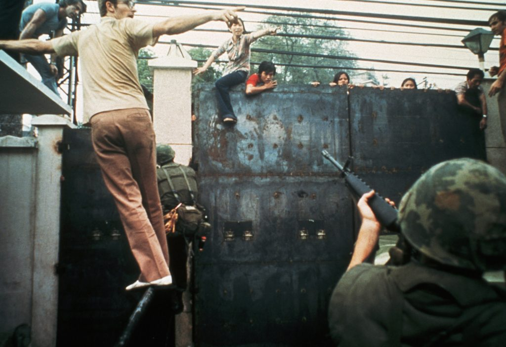 US Embassy April 29, 1975 1975, Ho Chi Minh City, Vietnam --- A soldier aiming his gun at South Vietnamese people climbing the gates of the United States Embassy in Saigon, South Vietnam. --- Image by © Nik Wheeler/CORBIS