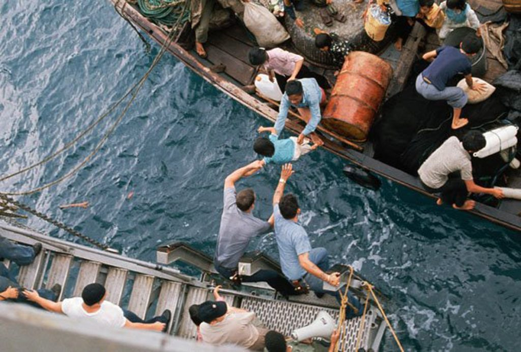 Fall of Saigon 1975 - Rescuing Vietnamese refugees South China Sea . . . Crewmen of the amphibious cargo ship U.S.S. Durham (LKA-114) take Vietnamese refugees aboard from a small craft. The refugees will be transferred later by mechanized landing craft (LCM) to the freighter Transcolorado.