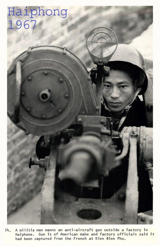 Một dân quân điều khiển khẩu súng phòng không bên ngoài một nhà máy tại Hải Phòng. Khẩu súng này do Mỹ chế tạo và các viên chức nhà máy nói nó đã tịch thu được từ người Pháp tại Điện Biên Phủ. 1967.