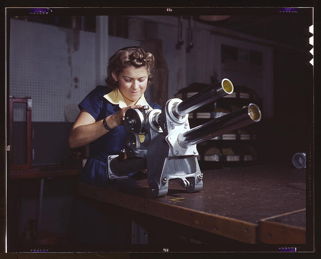 Palmer, Alfred T.,, photographer.   A young woman employee of North American Aviation, Incorporated, working over the landing gear mechanism of a P-51 fighter plane, Inglewood, Calif. The mechanism resembles a small cannon   1942 Oct.
