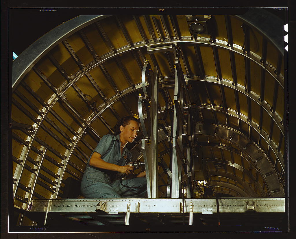 Hollem, Howard R.,, photographer.   Production of B-24 bombers and C-87 transports, Consolidated Aircraft Corp., Fort Worth, Texas. Cabbie Coleman, former housewife, works at western aircraft plant. Installing of oxygen racks above the flight deck   1942 Oct.