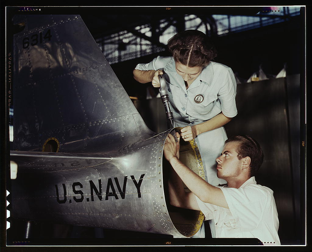 Mrs. Virginia Davis, a riveter in the assembly and repair department of the Naval air base, supervises Chas. Potter, a NYA trainee from Michigan, Corpus Christi, Texas.