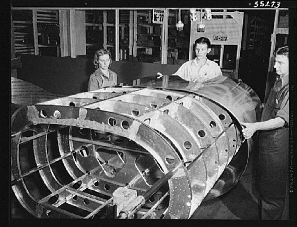 The skin is applied to the frame of a tank for a B-25 bomber. Women found in every department at North American Aviation, working together and with men. Next year 80 percent will be women 20 percent at present