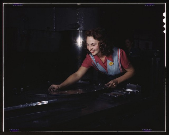 A woman preparing metal parts to go through a multi-ton hydropess. North American Aviation, Inc. 1942.