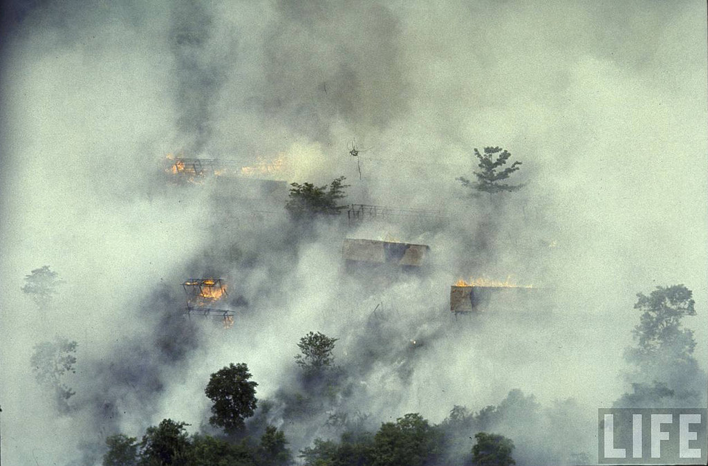 Smoke rising from cluster of thatched huts following bombing and resulting fire from napalm in Vietcong territory during Vietnam War. Location: Vietnam Date taken: 1966 Photographer: Larry Burrows