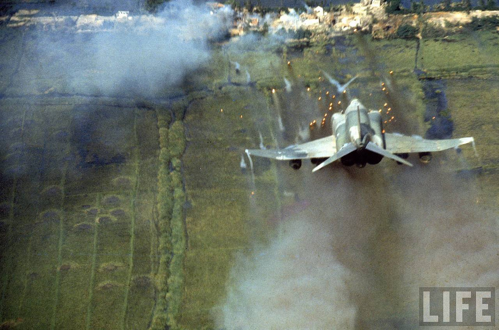 American F-4C Phantom jet firing rockets into small village known to be an important Vietcong stronghold during the Vietnam War. Location: Vietnam Date taken: 1966 Photographer: Larry Burrows