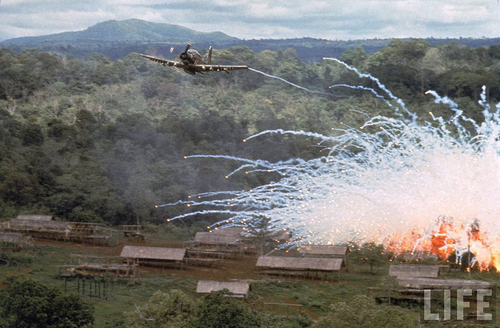 Small village bursting into flame under a spread of phosphorus explosives dropped during an American air strike against Viet Cong positions. Location: Vietnam Date taken: 1966 Photographer: Larry Burrows