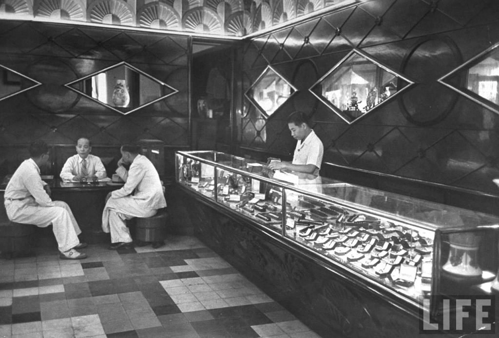 SAIGON 1948 - Man watching shop in store while others sit and talk, in French Indochina Photo by JACK BIRNS