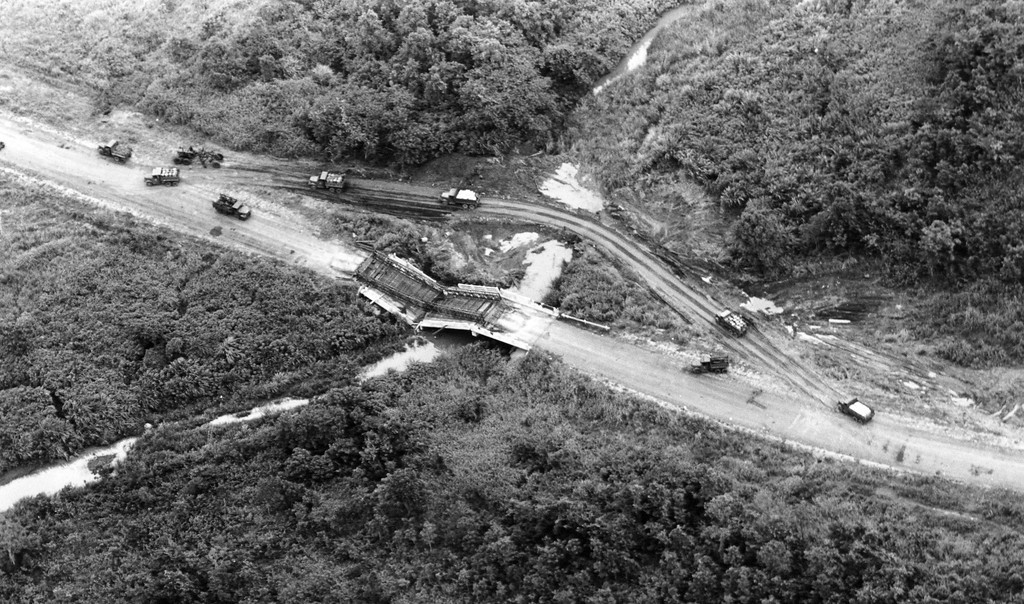 South Vietnamese supply trucks take a detour around a destroyed bridge en route to Pleiku on Route 19, July 18, 1965. The original bridge, and a temporary bridge placed on top of it, were both destroyed by the Viet Cong. (AP Photo/Eddie Adams)
