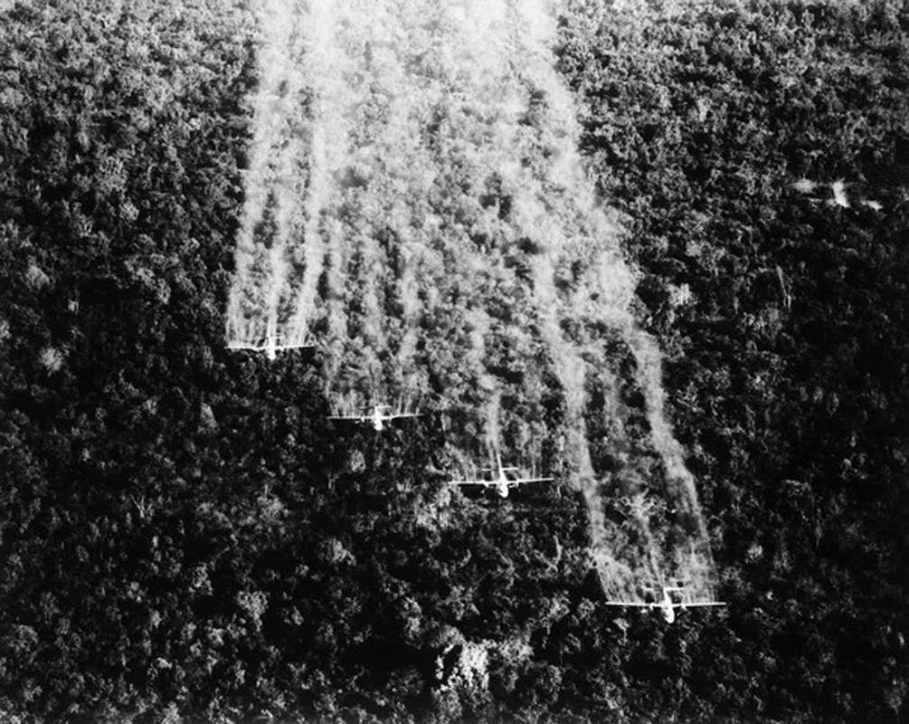 30 Sep 1965, Tan Son Nhut, South Vietnam --- 9/30/1965-Tan Son Nhut, South Vietnam: A flight of four United States Air Force Ranch Hand C-123s spray a Viet Cong jungle position near here with a defoliating liquid. The four specially equipped aircraft cover a swath of more than 1,000 feet wide on each pass over the dense jungle. --- Image by © Bettmann/CORBIS