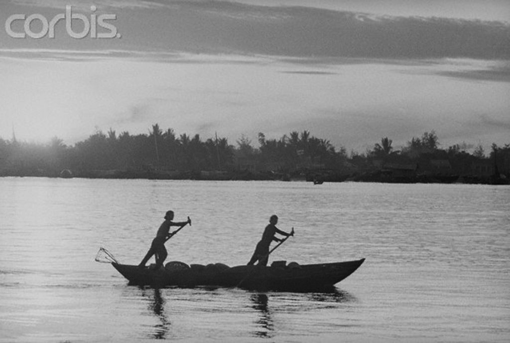 29 Jul 1965, South Vietnam --- Two Vietnamese fishermen paddle through the Mekong Delta at sunset. --- Image by © Bettmann/CORBIS