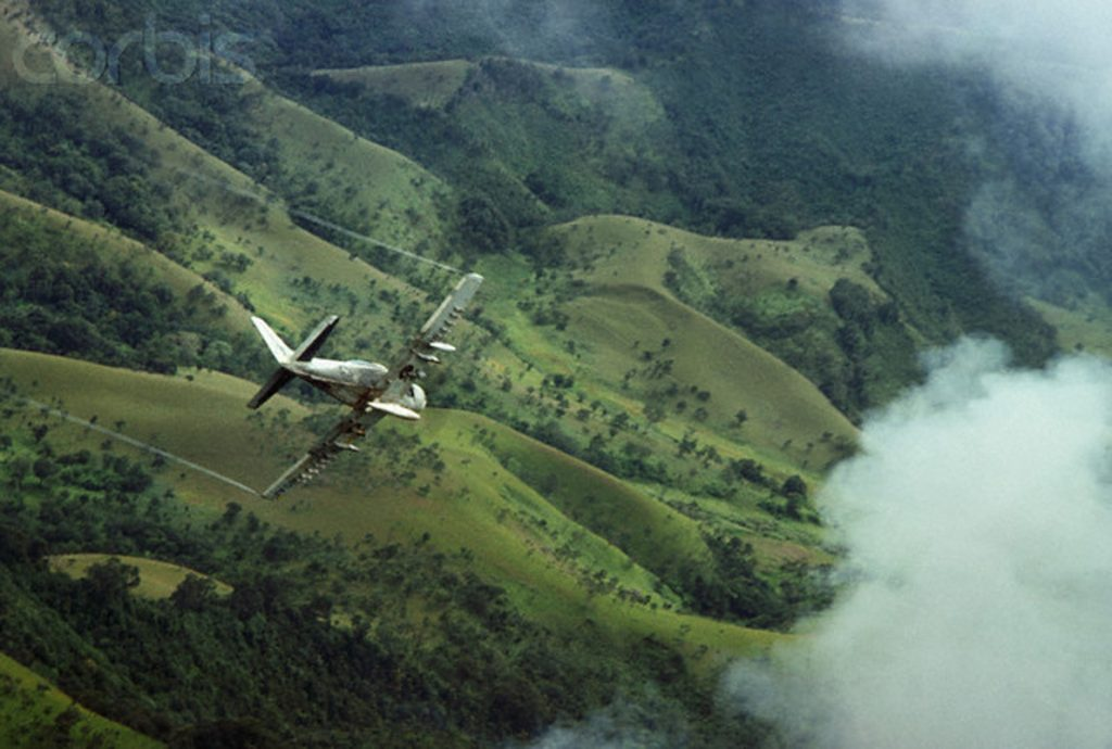 ca. 1966, Vietnam --- An aerial view of a US Skyraider military aircraft dive bombing over Vietnamese hills. --- Image by © Tim Page/CORBIS