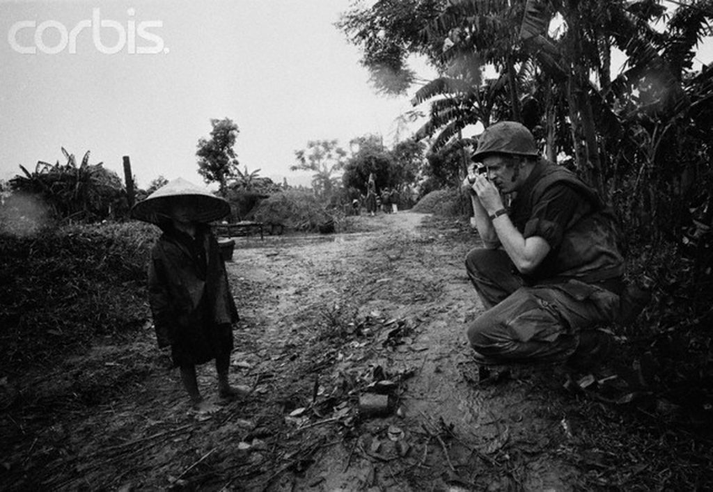1966, South Vietnam --- A U.S. soldier photographs a child in the Mekong Delta during Operation Search and Destroy. --- Image by © Christian Simonpietri/Sygma/CORBIS