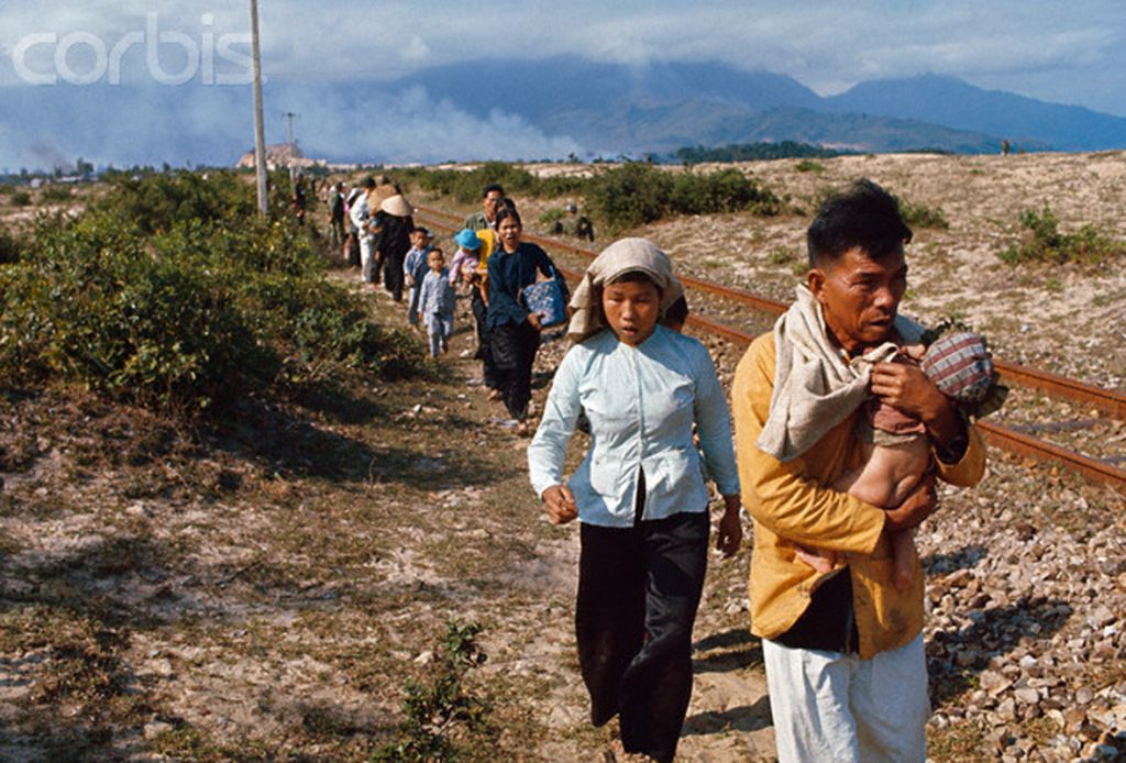 February 1968, Nemo, South Vietnam --- Refugees stream out of the city over a road that has been partially blocked with logs and furniture put there by the Viet Cong. --- Image by © Bettmann/CORBIS