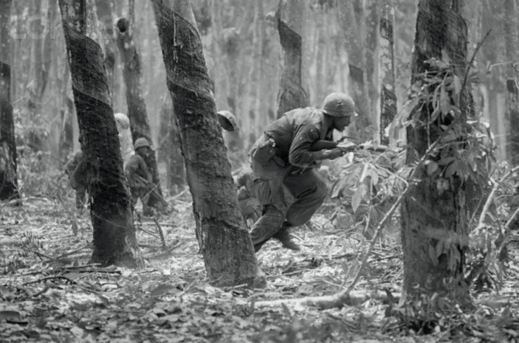 04 Mar 1969, East of Dau Tieng, South Vietnam --- Tay Ninh, South Vietnam: A trooper of the U.S. 1st Cavalry charges between rubber trees during an assault on a Viet Cong bunker complex inside the Michelin rubber plantation, five miles east of Dau Thieng. --- Image by © Bettmann/CORBIS