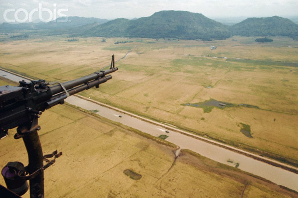 1969, Camodia-Vietnam border --- A military plane passes over a barren river plain at the Vietnamese-Cambodian border. Vietnam, 1969. --- Image by © Tim Page/CORBIS
