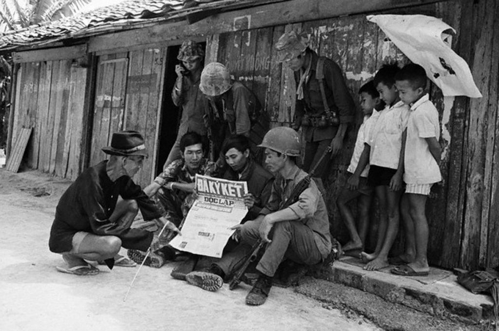 15 Jun 1973, Near Saigon, South Vietnam --- Saigon: Government troops and villagers read a newspaper with headline reporting cease-fire, signed in Paris June 14, a moment before the new cease-fire agreement goes into effect. The government troops were searching, house-to-house, to prevent the Communists from infiltrating a small hamlet along Highway 1, west of Saigon. 6/15/1973 --- Image by © Bettmann/CORBIS