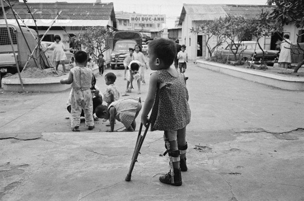 12 Dec 1971, Saigon, South Vietnam --- Saigon: Vietnam's War Orphans. Her frail body supported by crutches and leg braces, a little girl at the Hoi Duc-Anh orphanage in Saigon watches other youngsters there playing in the courtyard. These children are among South Vietnam's 100,000 orphans, most of whom are victims of the war. --- Image by © Bettmann/CORBIS