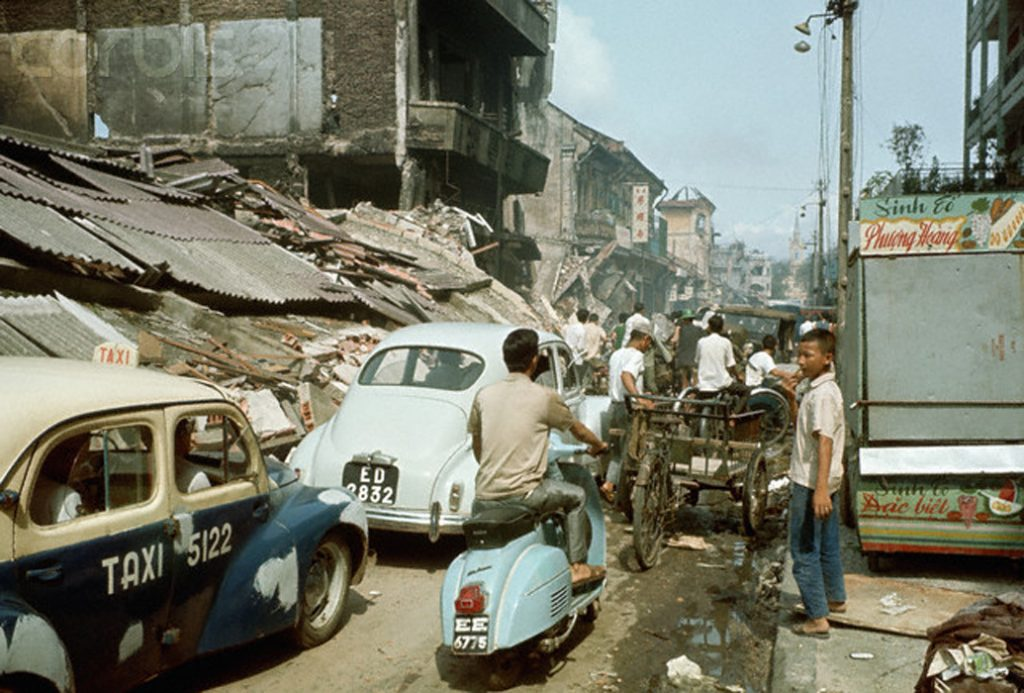 10 Jun 1968 Cholon, Vietnam- Vietnam War. Photo shows the Cholon area after major portion of fighting was over. Here, taxis and a moped are shown passing a flattened building. --- Image by © Bettmann/CORBIS